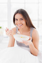 Having a breakfast in bed cheerful young smiling woman and smiling at camera Royalty Free Stock Image
