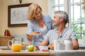Having breakfast at home happy mature wife serving bread to her husband for Royalty Free Stock Photo