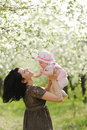 Having fun in garden laughing mother holding her giggling daughter Royalty Free Stock Photo