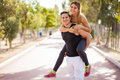 Having fun with my girlfriend handsome young men giving a piggyback ride to his Royalty Free Stock Photos