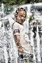 Having fun in summer fountain chinese little boy playing on square hot Royalty Free Stock Image