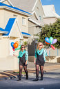 Having fun two friends wearing matching clothes strolling down the street each holding colorful balloons Stock Photos