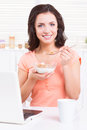 Having a healthy breakfast beautiful young woman and smiling while sitting at the kitchen table with laptop on it Royalty Free Stock Images