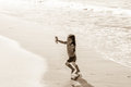 Having whale time lovely little girl runs away oncoming surf Stock Photography