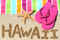 Hawaii beach travel concept written in sand with water next to towel and summer sandals and starfish hawaiian Stock Photography