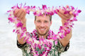 Hawaii caucasian man with welcome hawaiian lei male tourist portrait holding flower necklace giving it to the camera as a Royalty Free Stock Photography