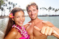 Hawaii couple happy on hawaiian beach woman wearing flower lei garland and men giving shaka aloha hand sign vacation travel Stock Photos