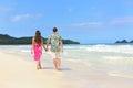 Hawaii honeymoon couple walking on tropical beach of newlyweds in hawaiian apparel pink sarong dress and green aloha shirt for Stock Image