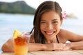 Hawaii woman with hawaiian mai tai drink on beach asian tourist swimming in infinity pool in bikini at beachfront resort Royalty Free Stock Photography