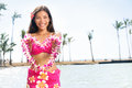 Hawaii woman showing flower lei garland of pink orchids beautiful smiling mixed race in bikini on beach giving a welcoming Stock Image
