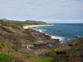Hawaiian coastline with surf crashing against lava rock outcropping Stock Images