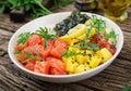 Hawaiian salmon fish poke bowl with rice, avocado, mango, tomato, sesame seeds and seaweeds. Royalty Free Stock Photo