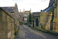 Haworth street scene west yorkshire england a behind the church in showing cobbles and stone built houses and the church door Stock Photography