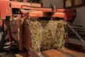Hay bale emerging from baling machine Royalty Free Stock Photos