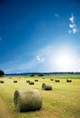 Hay bales in recently harvested field with blue sky Stock Image