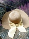 Hay hat and beautiful ribbin in garden chair in flower garden Royalty Free Stock Photo