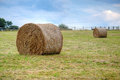 Hay stacks on a field with blue sky Stock Photo