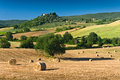 Haycock and trees in sunny tuscan countryside italy a small farm on a hill is visible the background Stock Photography