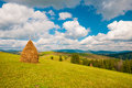 Haystack on mountain meadow with blue cloudy sky. Ukraine, Europe Royalty Free Stock Photo