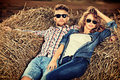 Haystack romantic young couple in casual clothes sitting together in Stock Images