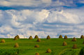 Haystacks on a green field and blue sky with cloud Stock Photo