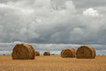 Haystacks under clouds on the field Royalty Free Stock Images