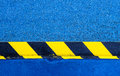 Hazard warning paint on floor yellow and black stripes painted a metal rail a blue Stock Image