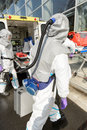 Hazardous material medical team with equipment walking towards contaminated building Stock Images