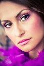 Hazel eyed model portrait of a beautiful brunette with dark brown eyes wearing magenta make up and covered in purple feathers Stock Images