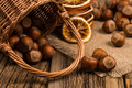 Hazelnuts in a basket on old wooden table.