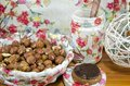 Hazelnuts in a decoupage decorated bowl on a table surrounded by kitchen dishes wooden Royalty Free Stock Image