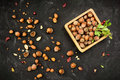 Hazelnuts in nutshell in a wooden box grunge dark backdrop cracked nuts autumn leaves background Royalty Free Stock Images