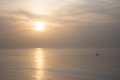 Hazy sunset and boat small sailboat sailing in the vastness of the mediterranian sea Royalty Free Stock Images