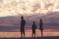 Hazy sunset silhouette three people against a over lake superior Stock Photo
