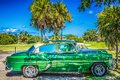 HDR - American green vintage car parked under palms in Varadero Cuba - Serie Cuba Reportage Royalty Free Stock Photo