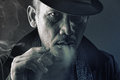 Hdr of evil crime lord with vicious eye portrait smoking a cigarette in Stock Photo