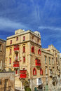 HDR photo of an old historic building with red balconies and windows and against a blue sky at Valletta, Malta Royalty Free Stock Photo