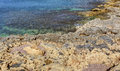 Hdr photo of a sunny day at the sea coast with deep blue clean water and a nice stone beach Royalty Free Stock Image