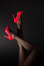 Head over high heels a pair of sexy legs in red kicked into the air on black background Stock Images
