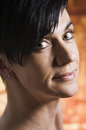Head of woman side close up a black haired middle age before orange hit erg round smiling looking into the camera Royalty Free Stock Photo