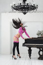 Headbanging go go dancer in pink costume standing room with piano Royalty Free Stock Images