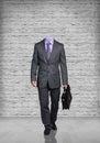 Headless businessman stand on gray brick background Stock Photo