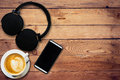 Headphone coffee and phone on wood background and texture Royalty Free Stock Photo