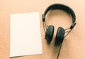 Headphone with white paper note on wood desk in music studio.