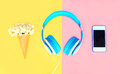 Headphones with ice cream cone flowers white smartphone over colorful yellow pink Royalty Free Stock Photo