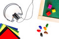 Headphones, school board, colored blocks, wax crayons, colored paper lying on a white wooden background. Headphones for studying l Royalty Free Stock Photo