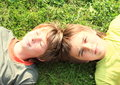 Heads of boys two smiling kids lying on green grass Royalty Free Stock Photography