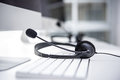 Headset with microphone on computer keyboard Royalty Free Stock Photo