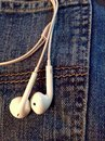 Headset sticking out of a denim pocket Stock Images