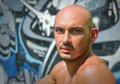 Headshot of bald young man shirtless outdoors in front graffiti wall Royalty Free Stock Images